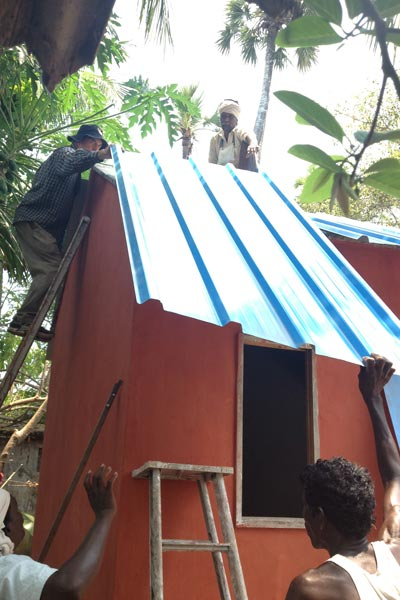 Babu working attatching roof sheeting on another hot roof.